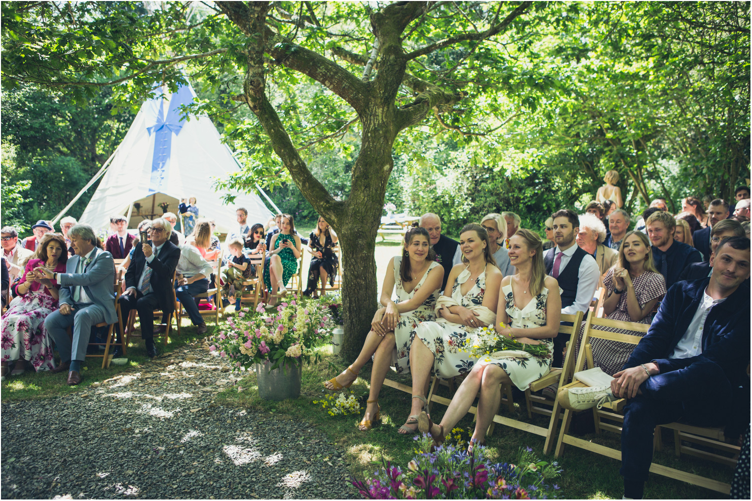 5 Wedding guests seated outside with event tipi in background