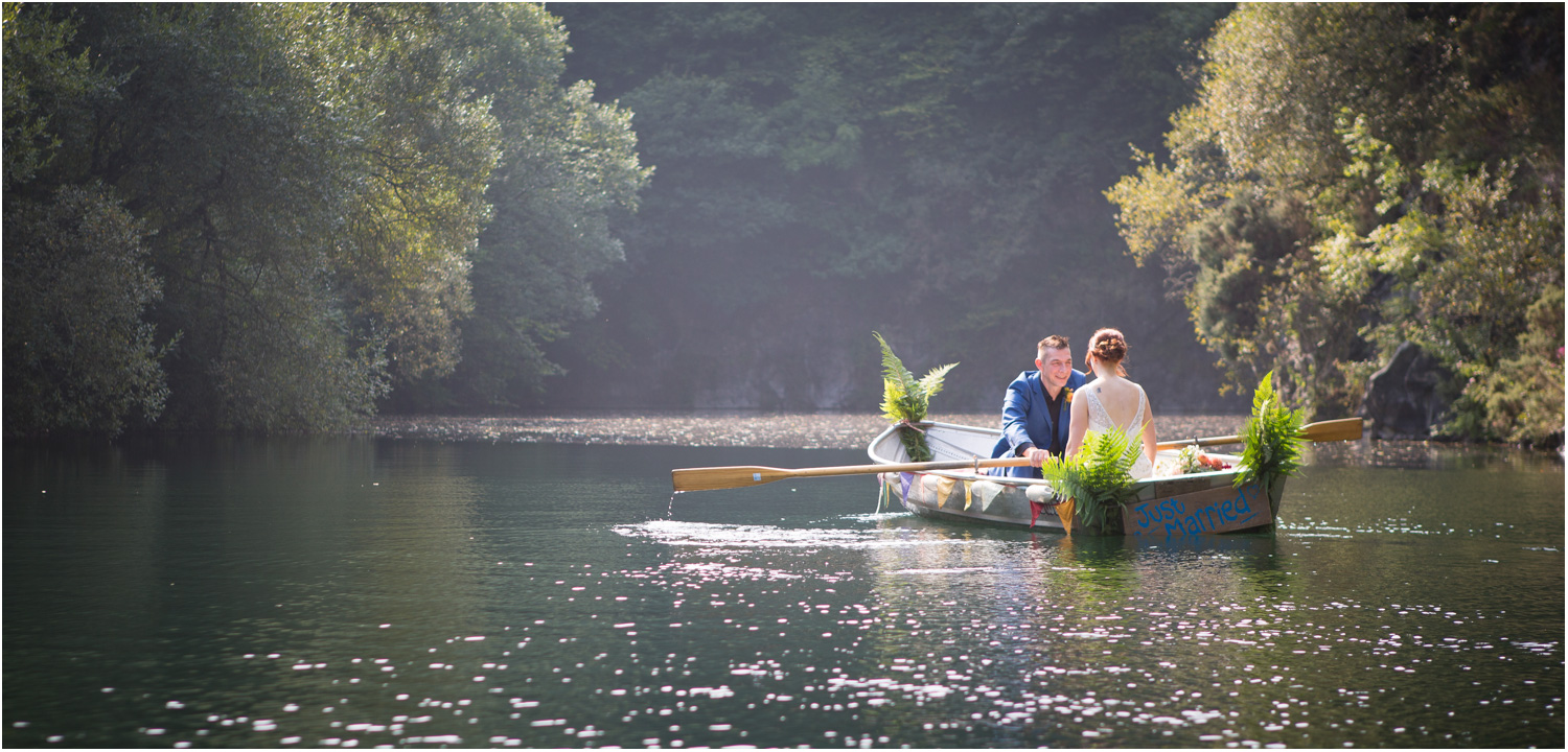 2 bride and groom in a boat decorated with ferns